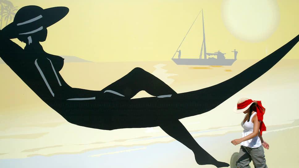 Туристка на фоне рекламного плаката в Афинах: не придет ли завтра виртуальный отдых на смену реальному?