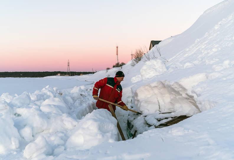Местный житель Алексей Черсунов раскапывает лодку после зимовки. Перед тем, как на реке вскроется лед, лодки обязательно нужно убрать в безопасное место, чтобы их не повредило и не унесло по течению