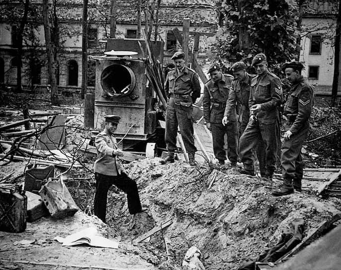 Русский офицер показывает британским союзникам, где нашли тела Адольфа Гитлера и Евы Браун. Берлин. Май 1945 года