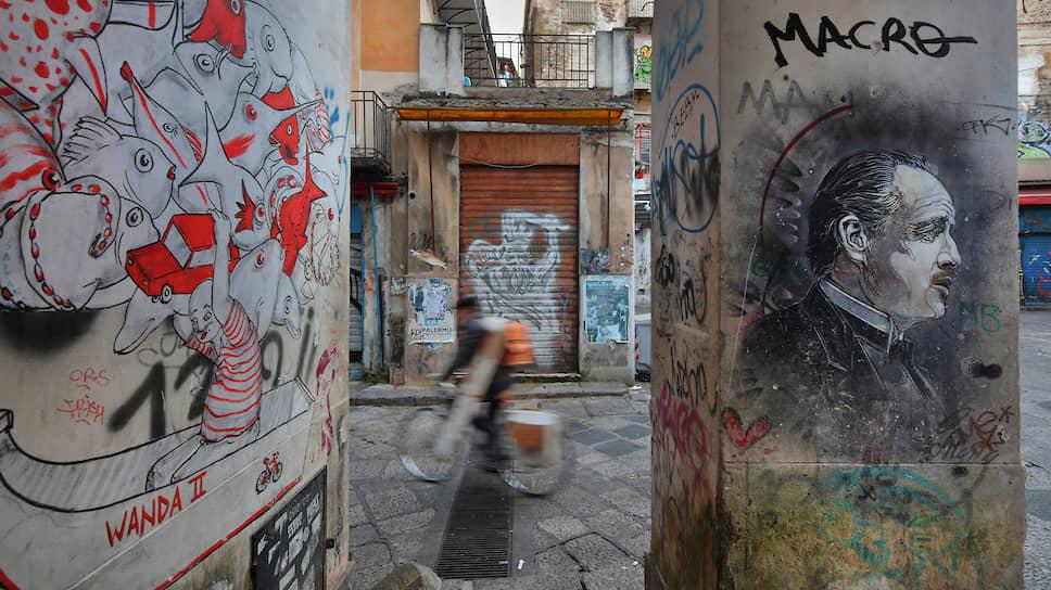 Даже когда города Италии немеют от карантина, их стены красноречивы. В этих граффити несложно увидеть намеки на мафию (справа — Марлон Брандо в роли Крестного отца). Беда в том, что ее новые боссы, как правило, изобретательнее стрит-арта