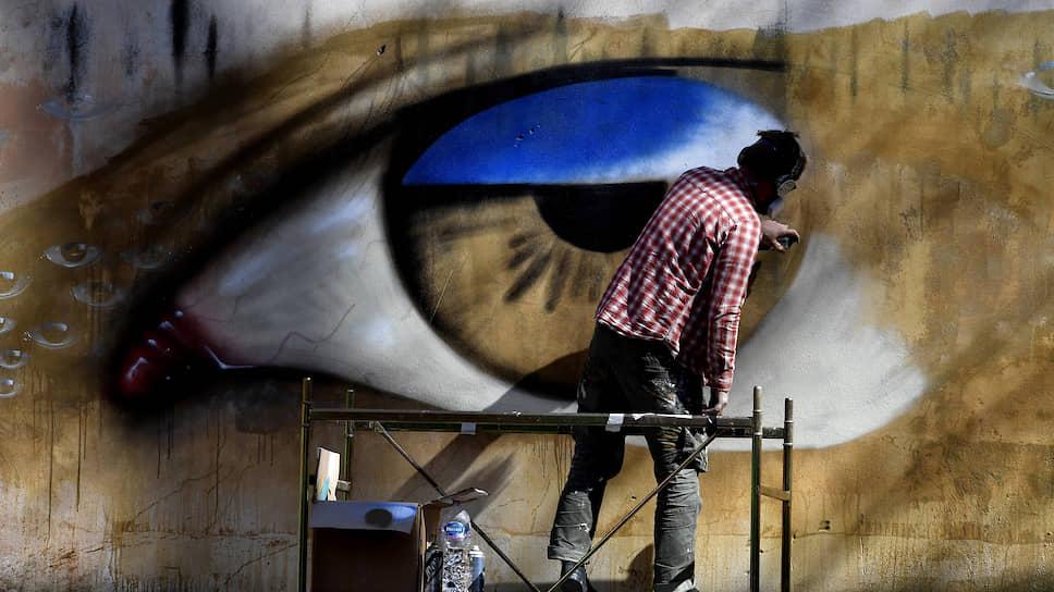 Беречь глаза при цифровом образе жизни становится все сложнее (на фото — уличный художник и его работа в Риме)