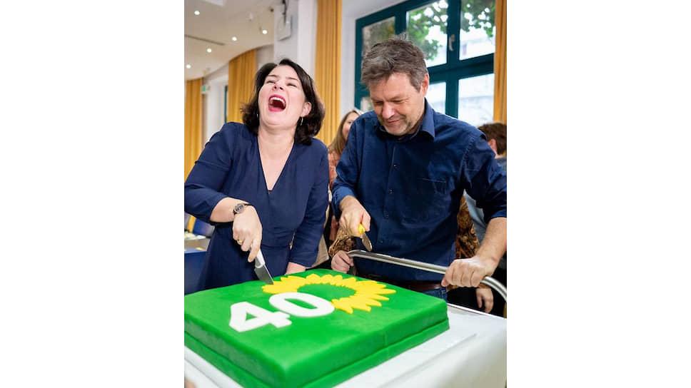 Претенденты на пост канцлера ФРГ от Партии зеленых Роберт Хабек и Анналена Бербок режут торт, испеченный в честь 40-летия своего партии