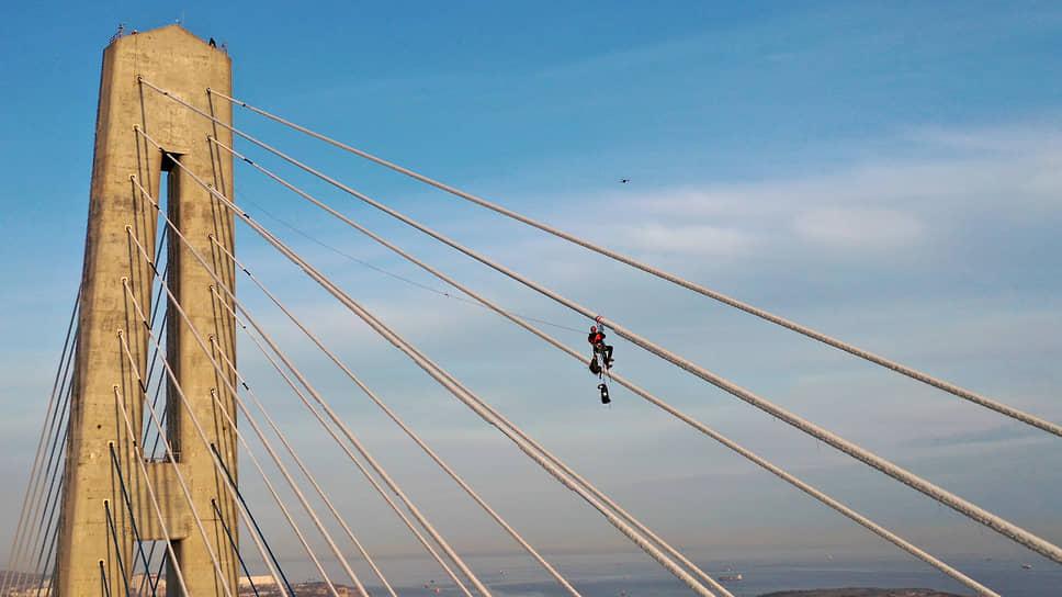 Можно подумать, что птичка примостилась на мостовых вантах. А вот и нет: это монтер вручную сбивает наледь с конструкции. Иначе никак