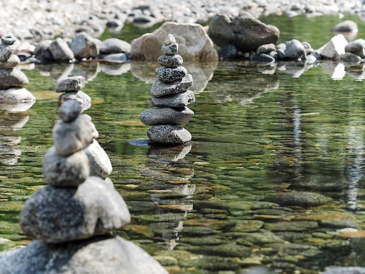 Внизу течет река Серебрянка, где туристы тоже оставляют пирамидки из камней
