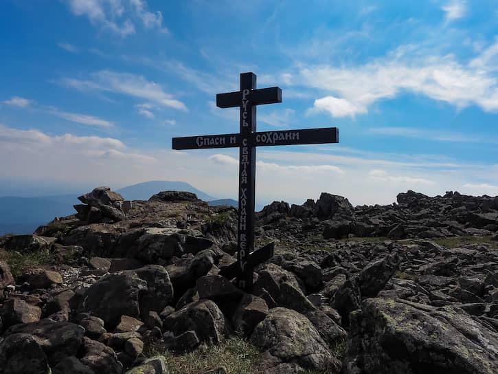 На вершине установлены разные памятные знаки. Православный крест