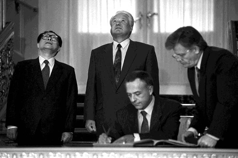 Министр иностранных дел России Андрей Козырев (сидит) во время встречи Президента России Бориса Ельцина (в центре стоит) и главы КНР Цзянь Цзэминя (слева). Встреча прошла в Кремле в 1994 году