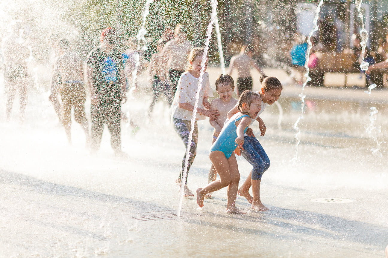 Местные дети спасаются от солнца в фонтанах на Центральной площади.
