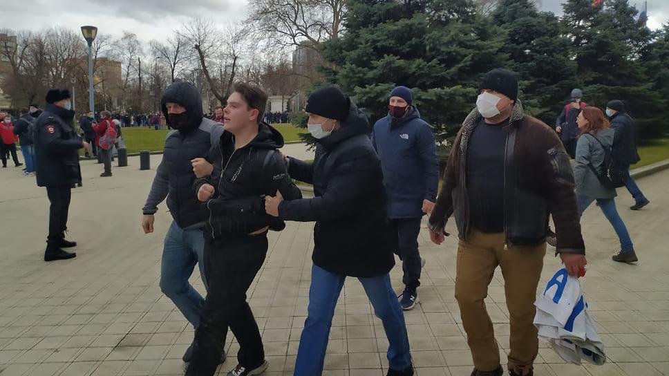 Люди в гражданском ведут парня к автобусу с задержанными