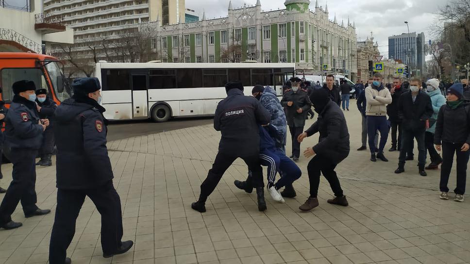 Задержанного несут в специальный автобус