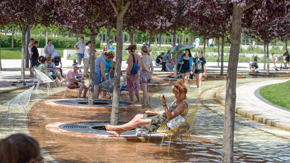 Люди отдыхают в тени декоративных слив Нигра (черная слива). Фонтанная аллея в парке «Краснодар»