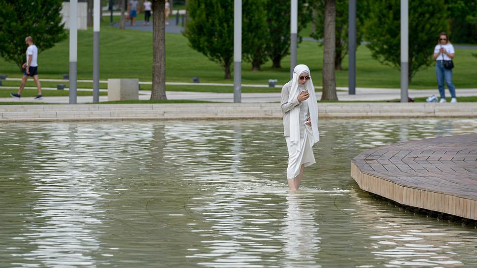 Босая девушка в хиджабе посреди искусственного водоема в парке «Краснодар»