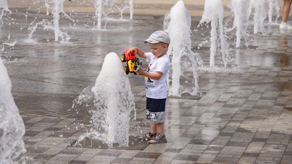 Мальчик играет в фонтане