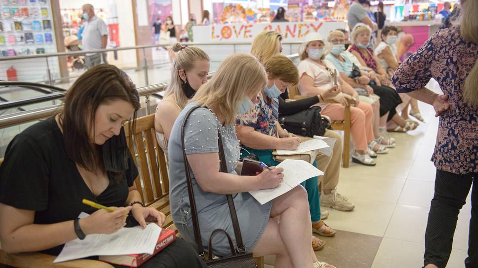 Краснодар, ТЦ «Красная Площадь». 30 июня, 13:00. Посетители, ожидающие своей очереди, заполняют бланки