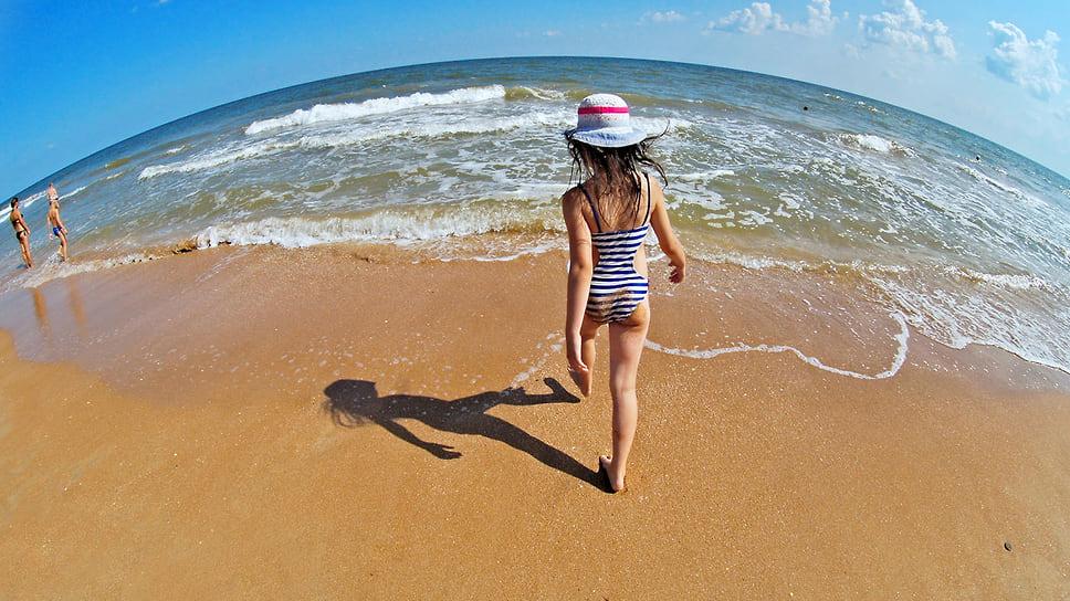 Маленькая девочка на берегу Азовского моря. Краснодарский край, Темрюкский район, пляж в поселке Пересыпь. Июль 2013 года