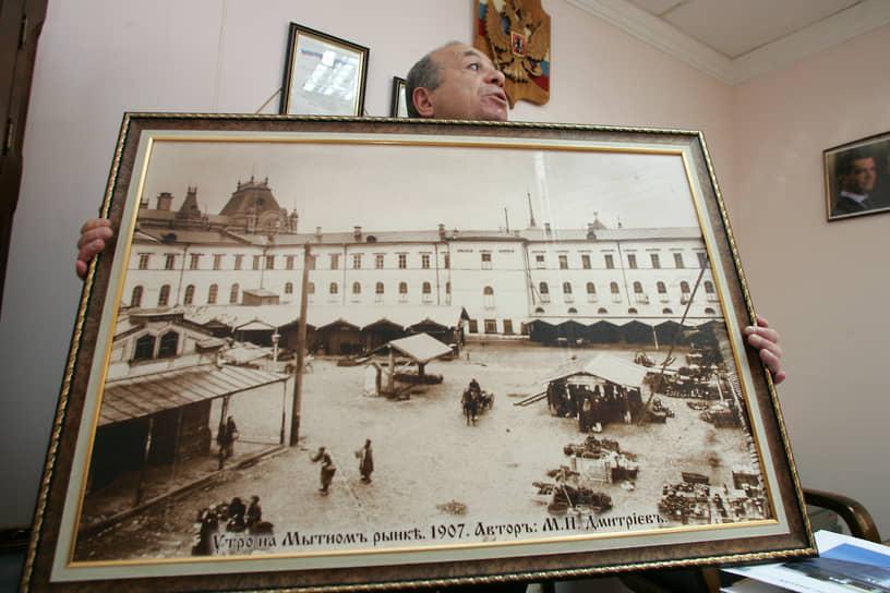 Собственник Мытного рынка Ваган Багдасарян с фотографией Максима Дмитриева, на которой изображен Мытный рынок 1907 года