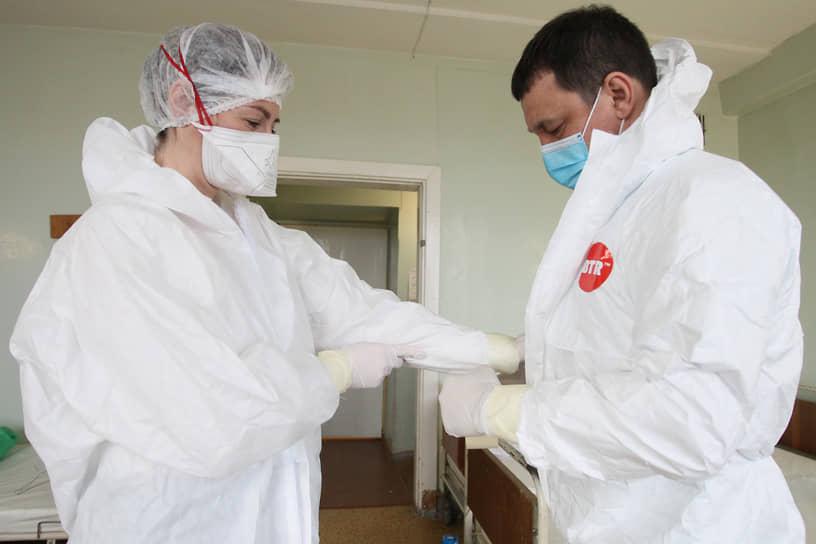 Процесс экипировки непростой, и врачи помогают друг другу, скрепляя элементы одежды скотчем