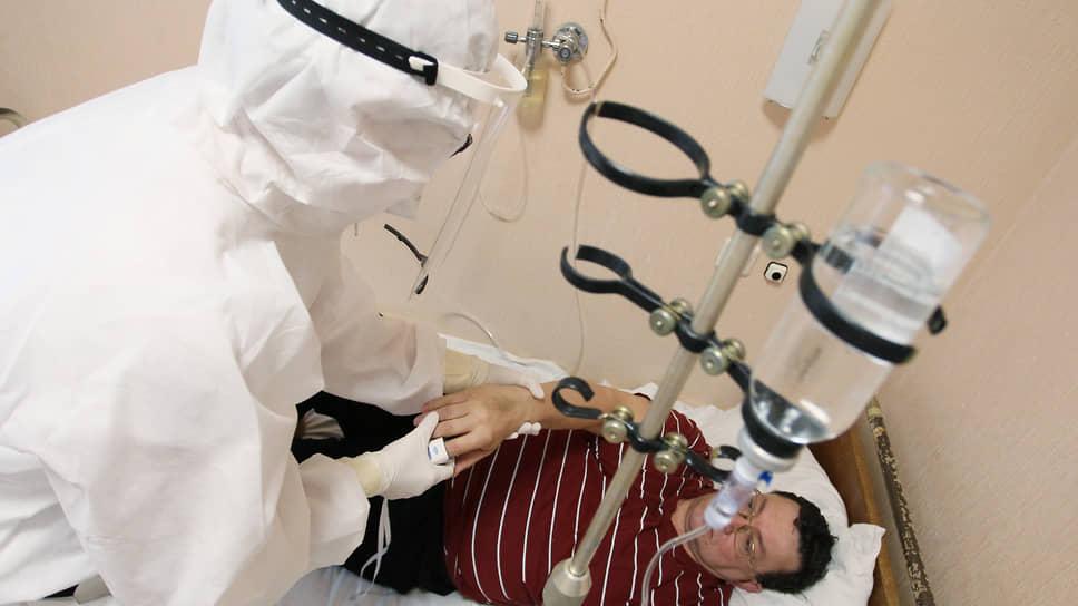 Среди обилия защитных костюмов странно видеть в больнице людей в обычной одежде. Это пациенты