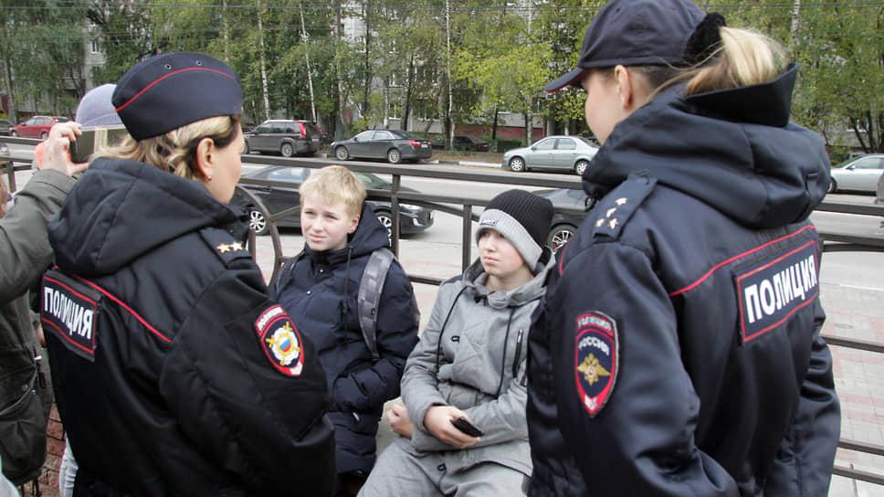 Сотрудницы полиции беседуют с несовершеннолетними подростками, участвующими в митинге
