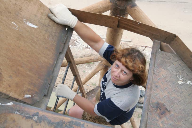Крановщица забирается в кабину башенного крана на стройке