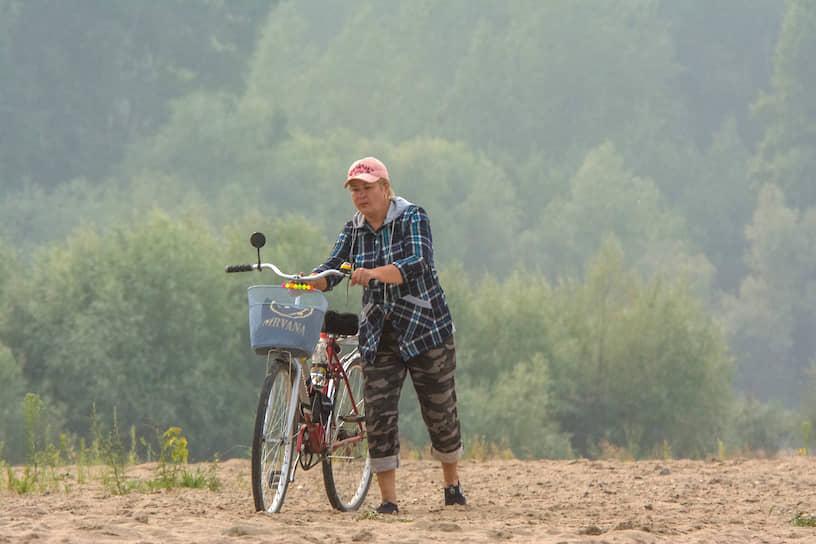 Женщина с велосипедом на фоне новосибирской дымки