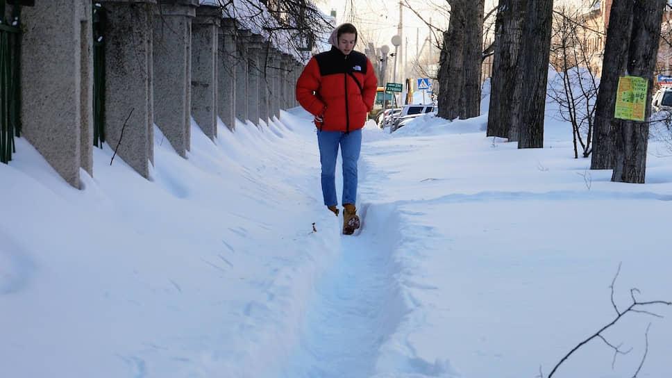 Житель Барнаула идет по расчищенной тропинке на улице Анатолия