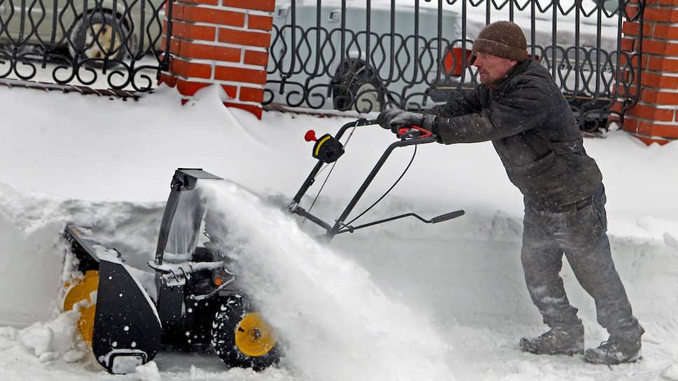 Работник коммунальной службы чистит тротуар от снега в центре Барнаула