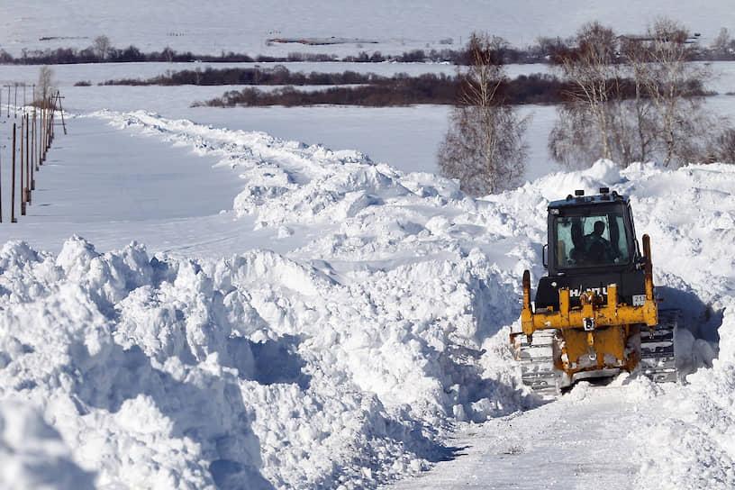 Спецтехника чистит занесенную снегом дорогу к селу Барановка Алтайского края