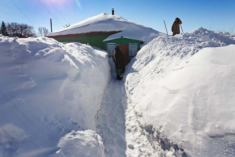 Последствия снегопадов в селе Барановка Змеиногорского района Алтайского края. Жительницы села чистят тропинку к дому