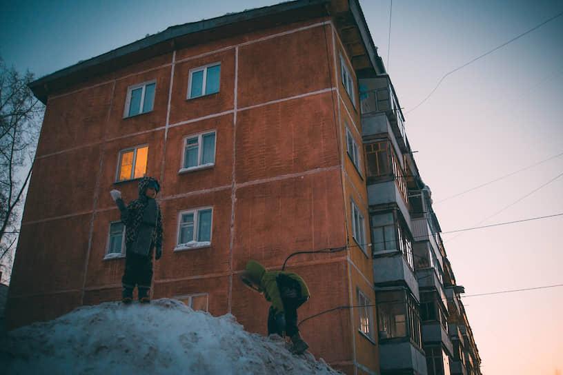 Дети играют на сугробе на улице Российской в новосибирском Академгородке