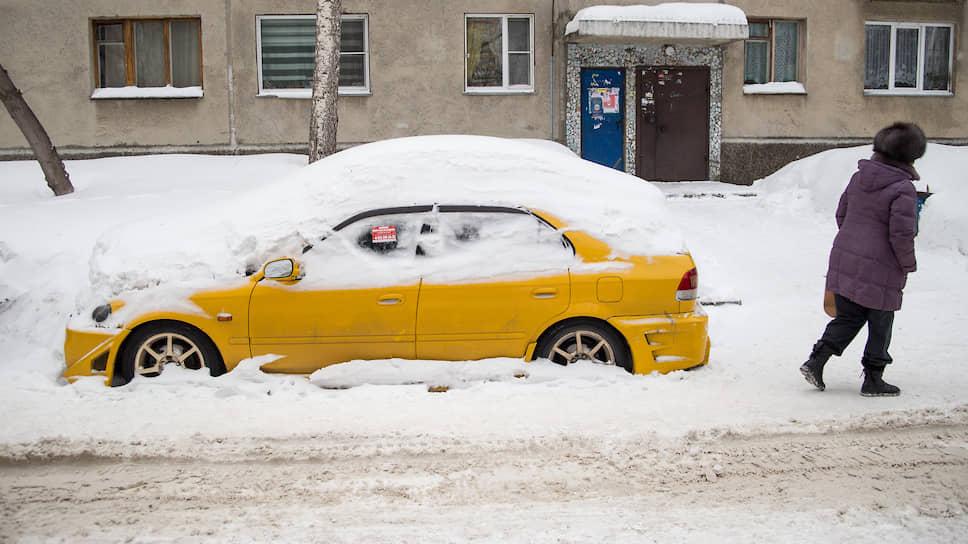 Занесенный снегом автомобиль во дворе дома в центре города