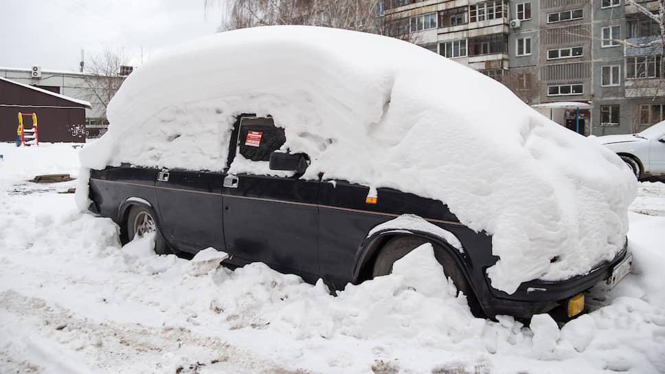 Занесенный снегом автомобиль во дворе дома