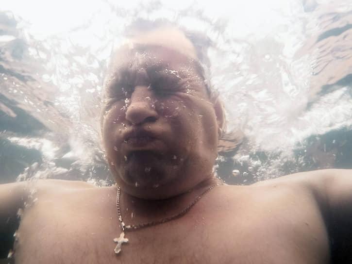 """<a href=""""/gallery/4224720"""">Празднование Крещения</a> в наукограде Кольцово (Новосибирской области). Верующий во время купания в купели на городском пруду"""