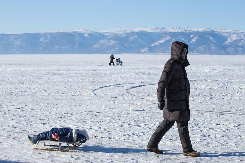 Мужчина везет ребенка на санках по замерзшему Байкалу