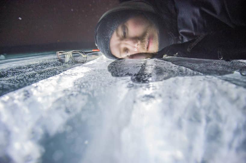 Мужчина лежит щекой на льду Байкала