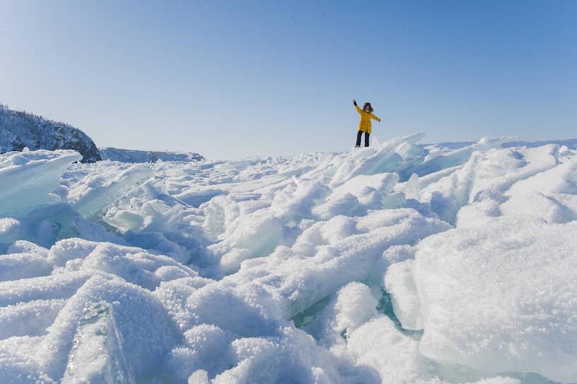 Человек стоит на ледяных торосах на побережье Байкала в районе мыса Хобой — самой северной точки острова Ольхон