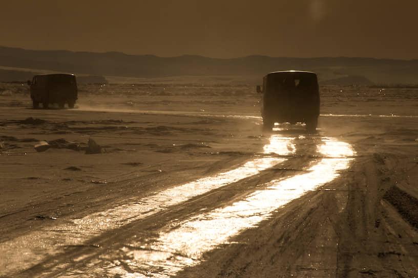 УАЗики, которые местные называют «буханки», едут по ледяной переправе Байкала во время заката