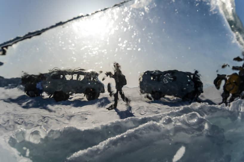 Силуэты машин и людей сквозь прозрачный лед на берегу Байкала