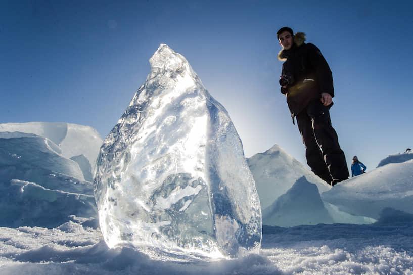 Турист смотрит на прозрачный массивный кусок льда на берегу Байкала