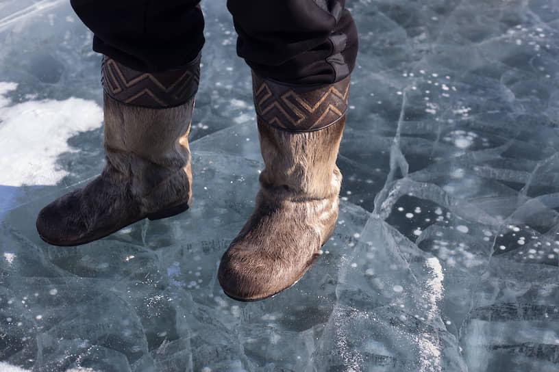 Местный житель стоит на льду в меховых унтах