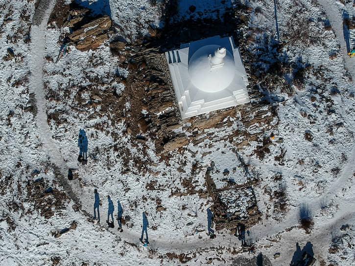 Тени людей на земле, которые совершают обход вокруг буддийской Ступы Просветления, на острове Огой на Байкале