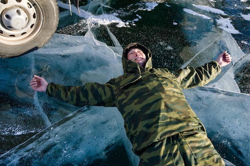 Мужчина лежит на льду Байкала