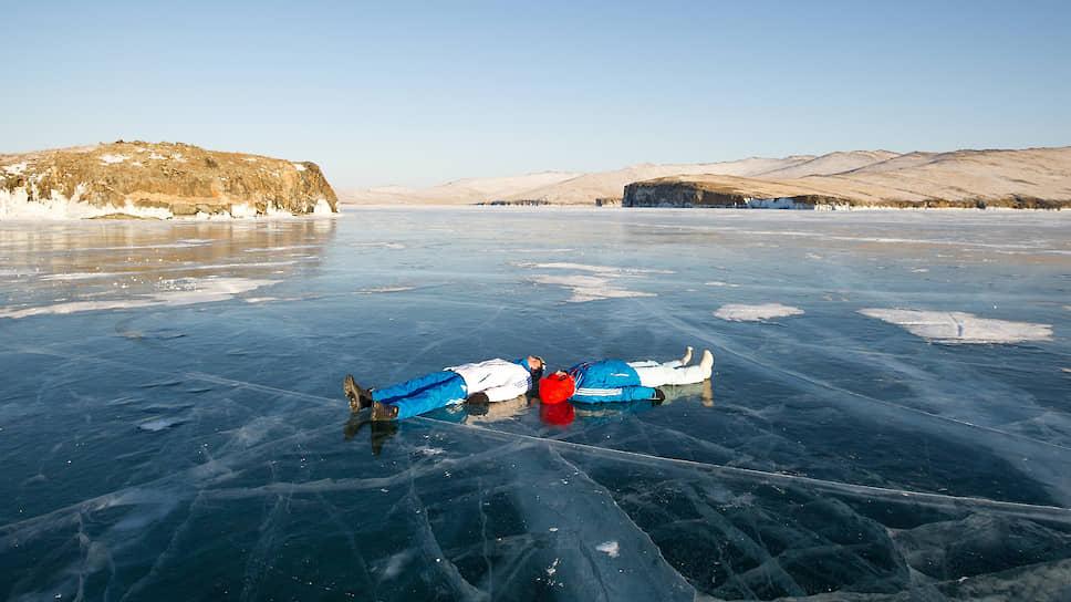 Люди лежат на прозрачном льду озера Байкал