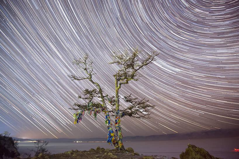 Звездное небо, снятое на длительной выдержке, и дерево с обрядовыми священными ленточками на скале Шаманка на берегу Байкала
