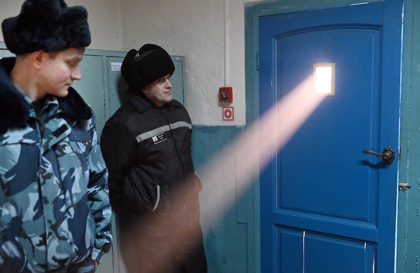 Осужденный и сотрудник охраны стоят перед дверью с окошком на входе в цех производства продуктов питания в исправительной колонии ИК-3 в Омске