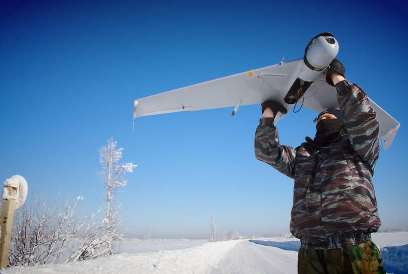 Сотрудник Росгвардии запускает беспилотник в тайге для выявления браконьеров и лесорубов, занимающихся незаконными вырубками леса, Алтайский край