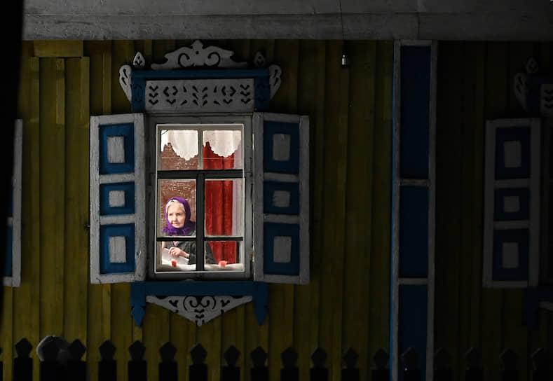 Пожилая женщина сидит у окна своего дома в деревне, Омская область