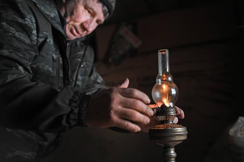 Охотник и лесовод греется в сторожке у керосиновой лампы. Таежная деревня Пихтовое в Омской области