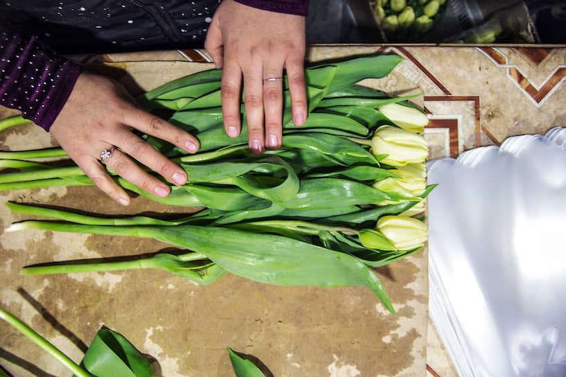 Работница тепличного хозяйства формирует из обрезанных от луковиц цветов букеты по 20 штук. Далее цветы отправляются в холодильник, а оттуда — на продажу