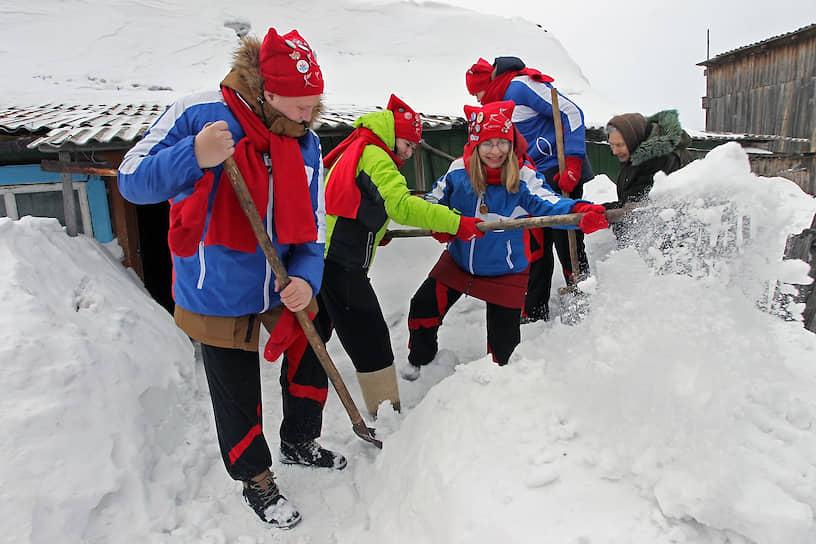 Участники волонтерской акции «Снежный десант» помогают ветерану села Белово в Алтайском крае откапывать дом от снега