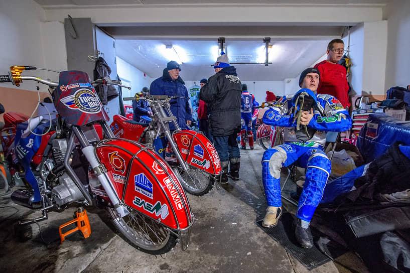 Спортсмены готовят мотоциклы в закрытом парке перед началом заездов